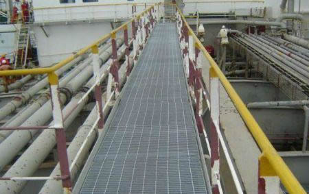 A serrated bar steel grating bridge connect the land and offshore workshop.